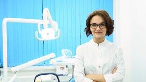 Ritratto delle armi stanti del bello dentista della giovane donna attraversate nel gabinetto dentario della clinica Medico sicuro fotografie stock