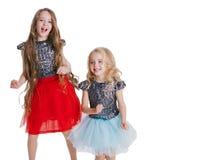 Ritratto delle bambine con il dancing riccio dell'acconciatura sul partito di festa in vestito con gli zecchini Celebrazione di c Fotografia Stock Libera da Diritti