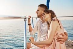 Ritratto delle coppie alla moda nell'amore, abbracciante mentre sedendosi sulla prua dell'yacht privato e godendo della vista del fotografia stock