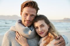 Ritratto delle coppie amorose che camminano insieme lungo la spiaggia di inverno fotografia stock
