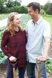 Ritratto delle coppie che lavorano nel campo organico dell'azienda agricola Fotografia Stock