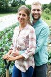 Ritratto delle coppie che lavorano nel campo organico dell'azienda agricola Immagini Stock Libere da Diritti