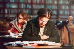 Ritratto delle coppie degli studenti in biblioteca Fotografie Stock Libere da Diritti