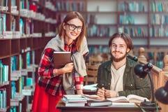 Ritratto delle coppie degli studenti in biblioteca Immagine Stock