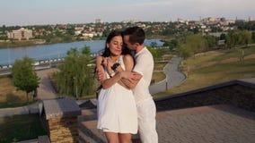 Ritratto delle coppie di amore nel parco di estate contro un paesaggio con il lago e la città archivi video