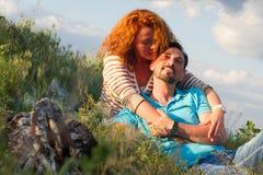 Ritratto delle coppie felici che mettono su coperta su erba vicino al camino sul fondo delle nuvole fotografie stock libere da diritti