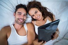Ritratto delle coppie felici con la compressa digitale che si trova sul letto Fotografia Stock Libera da Diritti
