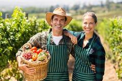 Ritratto delle coppie felici dell'agricoltore che tengono un canestro delle verdure Immagini Stock Libere da Diritti