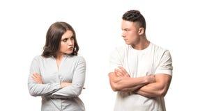 Ritratto delle coppie infelici turbate che giudicano armi attraversate e che si guardano isolato su fondo bianco Negativo fotografie stock libere da diritti