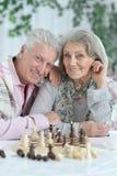 Ritratto delle coppie senior felici che giocano insieme scacchi fotografia stock