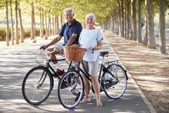 Ritratto delle coppie senior sorridenti che ciclano sulla strada campestre fotografia stock libera da diritti
