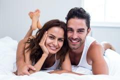Ritratto delle coppie sorridenti che si trovano sul letto Fotografia Stock