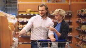 Ritratto delle coppie sveglie felici che scelgono i pani freschi in supermercato archivi video