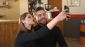 Ritratto delle coppie in un caffè, prendono un selfie e godono di un cappuccino fragrante archivi video