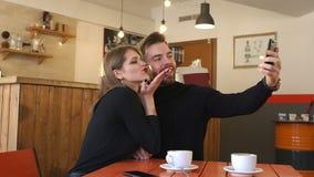 Ritratto delle coppie in un caffè, prendono un selfie e godono di un cappuccino fragrante stock footage