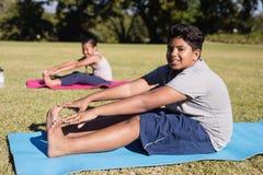 Ritratto delle dita del piede commoventi del ragazzo durante il vetro di yoga Immagine Stock Libera da Diritti