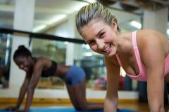 Ritratto delle donne adatte sorridenti che fanno allungando esercizio sulla stuoia Fotografia Stock Libera da Diritti