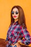 Ritratto delle donne della gioventù in occhiali da sole con trucco perfetto hipster Fondo arancio Urbano fotografia stock