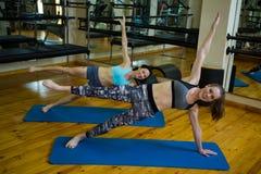 Ritratto delle donne di misura che eseguono allungando esercizio Immagine Stock Libera da Diritti
