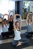 Ritratto delle donne di misura che eseguono allungando esercizio Immagine Stock