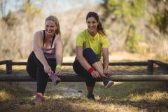 Ritratto delle donne felici che indossano le scarpe dopo l'allenamento durante la corsa ad ostacoli Fotografia Stock Libera da Diritti