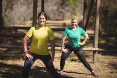 Ritratto delle donne felici che si esercitano durante la corsa ad ostacoli Fotografie Stock