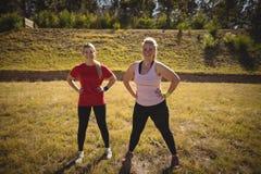 Ritratto delle donne felici che si esercitano durante la corsa ad ostacoli Immagini Stock