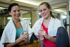 Ritratto delle donne felici che tengono bottiglia di acqua mentre rilassandosi dopo l'allenamento Fotografia Stock Libera da Diritti