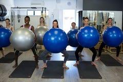 Ritratto delle donne sorridenti che si esercitano sulla palla di forma fisica Immagine Stock