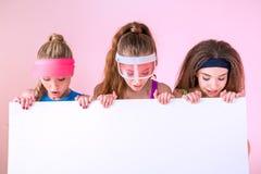 Ritratto delle donne sportive che esaminano insegna in mani Fotografie Stock Libere da Diritti