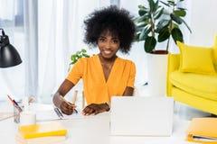 ritratto delle free lance afroamericane sorridenti nel luogo di lavoro con il computer portatile ed il taccuino fotografia stock libera da diritti