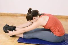 Ritratto delle gambe streching della donna di sport Fotografia Stock