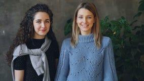 Ritratto delle giovani donne attraenti che stanno insieme in appartamento del sottotetto, sorridenti ed esaminanti macchina fotog archivi video