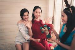 Ritratto delle ragazze asiatiche che danno a regalo di sorpresa ai suoi amici i fotografia stock