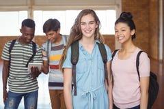 Ritratto delle scolare che stanno con il compagno di classe con i compagni di classe nel fondo Immagine Stock