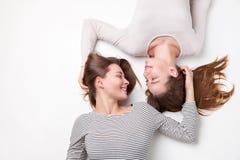 Ritratto delle sorelle felici che si trovano sul pavimento Fotografia Stock Libera da Diritti