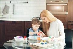 Ritratto delle uova di Pasqua felici della pittura della giovane donna con il suo piccolo figlio adorabile fotografie stock libere da diritti