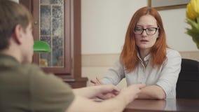 Ritratto dello psicologo adorabile della donna che ha sessione con il suo paziente Bello psicologo dai capelli rossi della donna  video d archivio