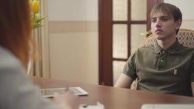 Ritratto dello psicologo adorabile della donna che ha sessione con il suo paziente Bello psicoterapeuta dai capelli rossi della d video d archivio