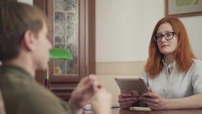Ritratto dello psicoterapeuta sveglio della giovane donna che ha sessione con il suo paziente Bello psicologo dai capelli rossi d stock footage
