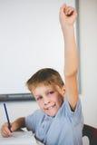 Ritratto dello scolaro che solleva la sua mano in aula Immagini Stock