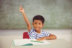 Ritratto dello scolaro che solleva la sua mano in aula Fotografia Stock Libera da Diritti