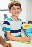 Ritratto dello scolaro che sorride nell'aula Immagini Stock Libere da Diritti