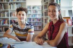 Ritratto dello scolaro felice che si siede con il suo compagno di classe in biblioteca Fotografia Stock Libera da Diritti