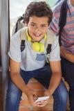 Ritratto dello scolaro felice che si siede sul davanzale della finestra e che utilizza telefono cellulare nel corridoio Fotografia Stock Libera da Diritti