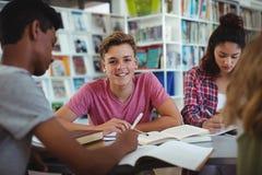 Ritratto dello scolaro felice che studia con i suoi compagni di classe in biblioteca Fotografie Stock