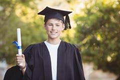 Ritratto dello scolaro laureato che sta con il rotolo di grado in città universitaria Immagine Stock