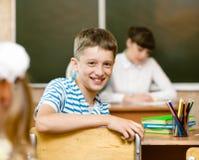 Ritratto dello scolaro nel luogo di lavoro con l'insegnante su fondo Fotografie Stock Libere da Diritti