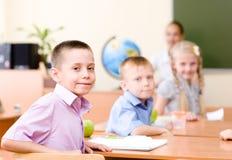 Ritratto dello scolaro nel luogo di lavoro con l'insegnante su fondo Fotografia Stock Libera da Diritti