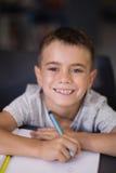 Ritratto dello scolaro sorridente che fa il suo compito in biblioteca Immagine Stock